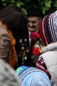 Een veteraan krijgt bloemen van omstanders nabij het monument voor de onbekende soldaat in Kiev. (foto Christie Miedema)